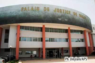 Attendant la délivrance d'un permis de visite, Abdoulaye Touré fume du yamba devant le bureau du doyen des juges.