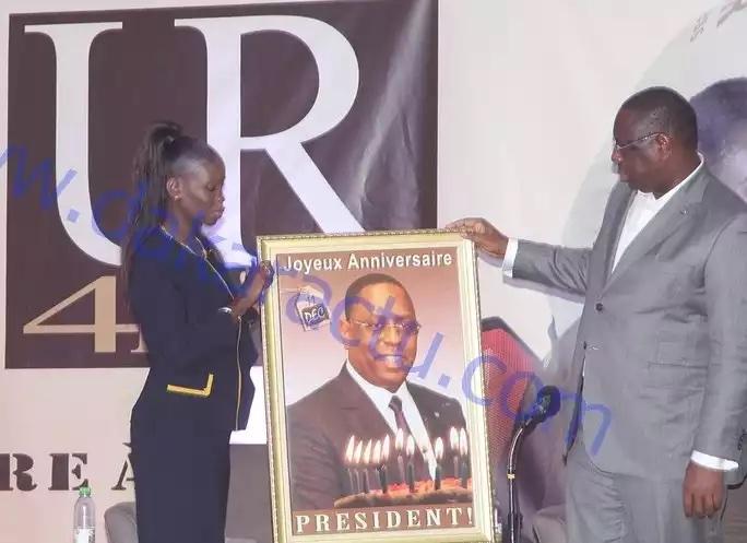La coordinatrice de la COJER Thérèse Faye Diouf donnant au président le cadeau d'anniversaire des jeunes au président Macky Sall